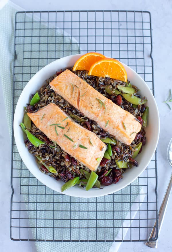 baked salmon with black rice in a big white bowl on a cooling rack