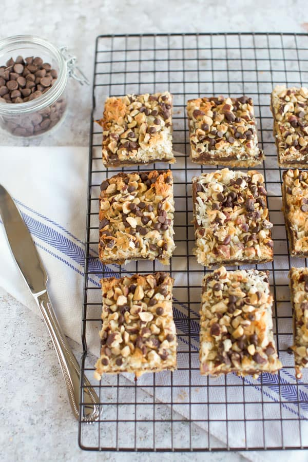 Gluten Free Seven Layer Bars on a cooling rack with a knife.