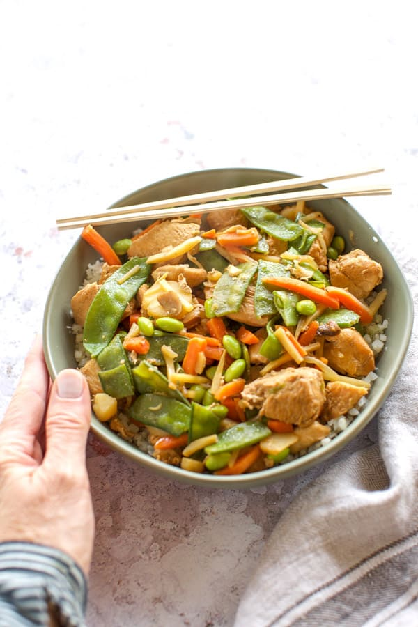 chicken stir fry in a green bowl with chopsticks