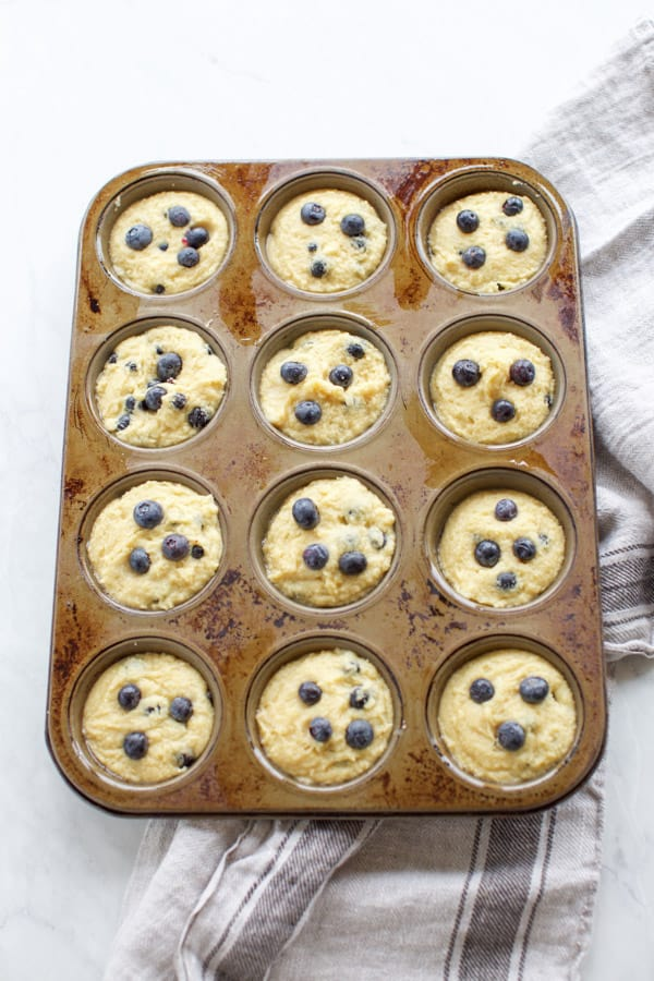 uncooked blueberry muffins in a muffin tin