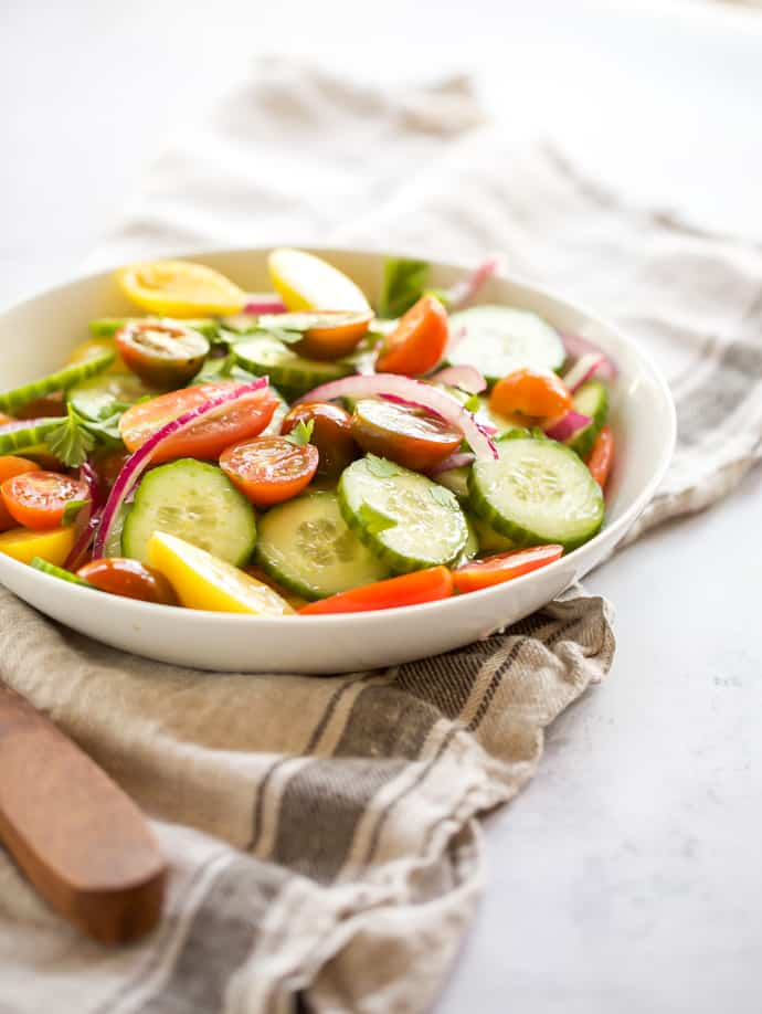 cucumber, tomato and onion salad with wooden spoon