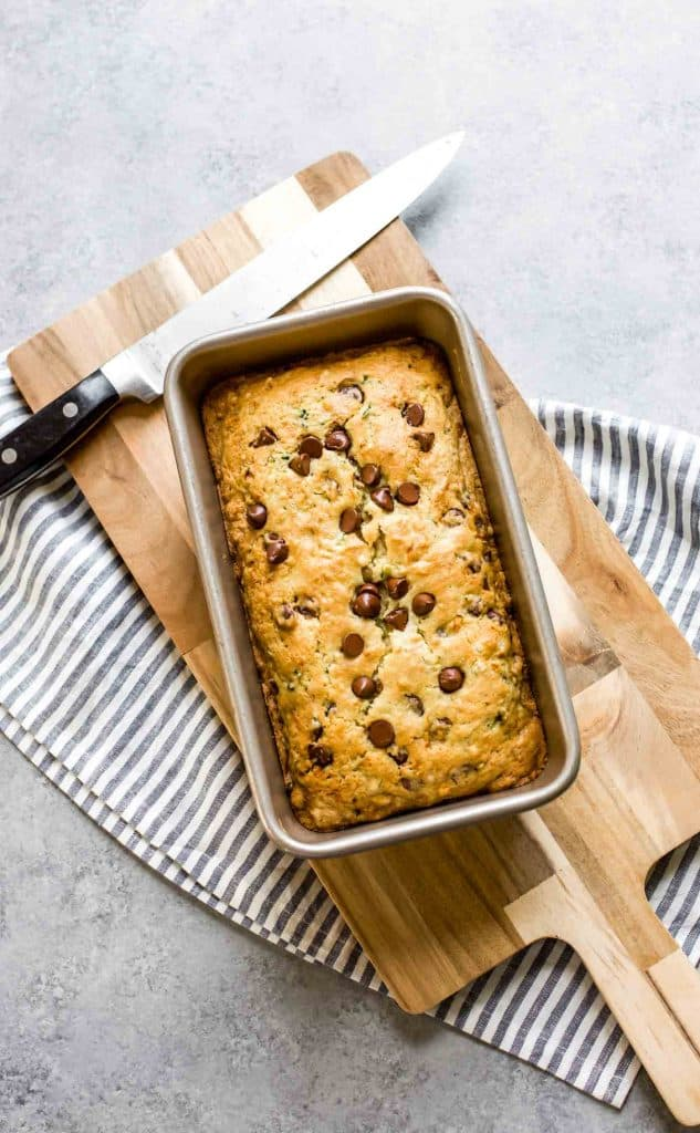 baked zucchini bread in a loaf pan with a knife