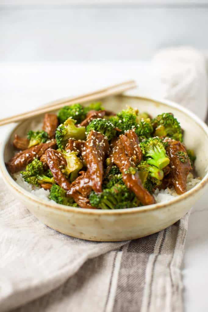 side view of beef and broccoli in a bowl with chopsticks
