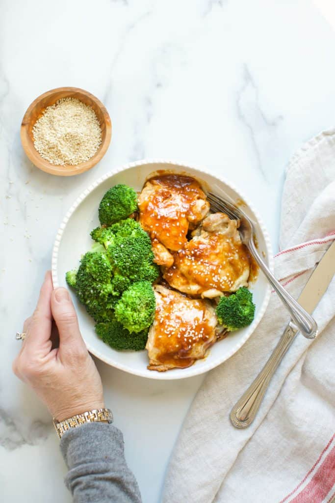 instant pot chicken teriyaki with sesame seeds with hands on the bowl