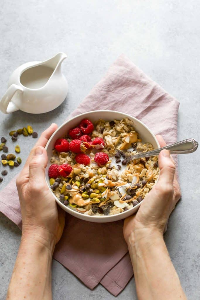 healthy oatmeal toppings in a bowl with two hands