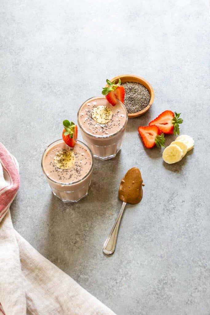 two strawberry smoothies in glasses with fruit and peanut butter on the side