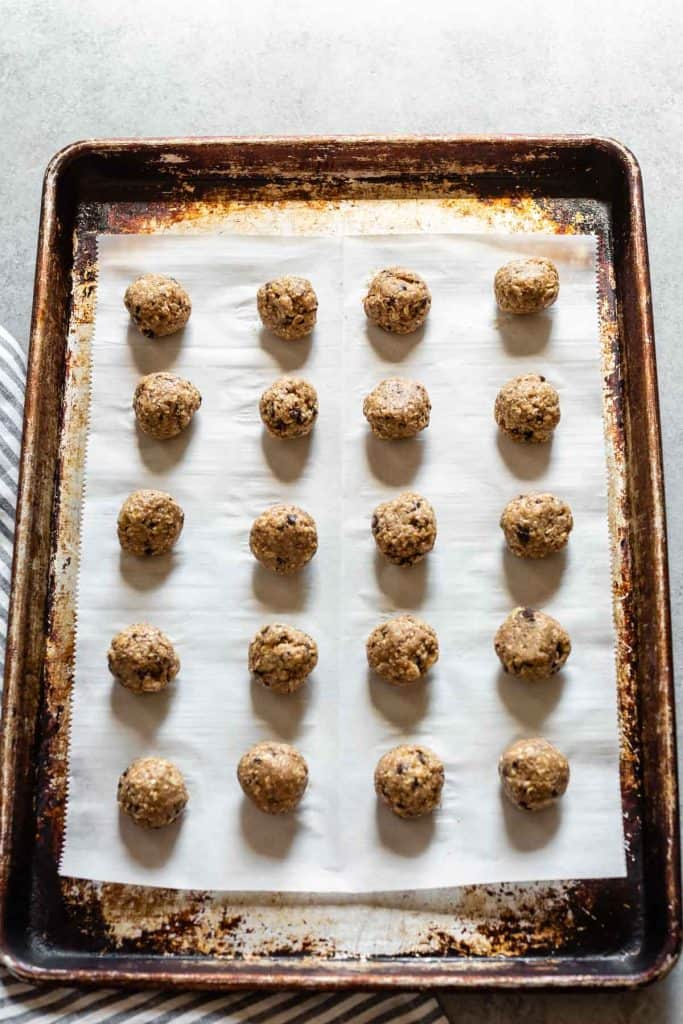 snack balls on parchment paper on a cookie sheet