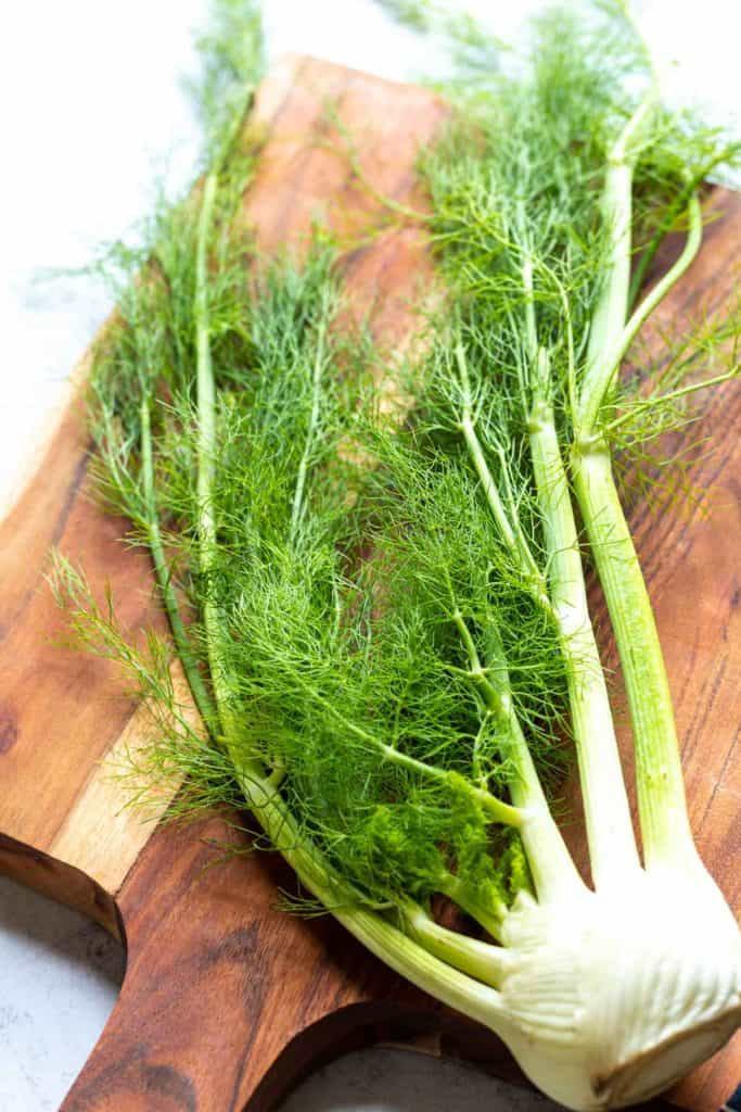large fennel bulb on a brown butcherblock board