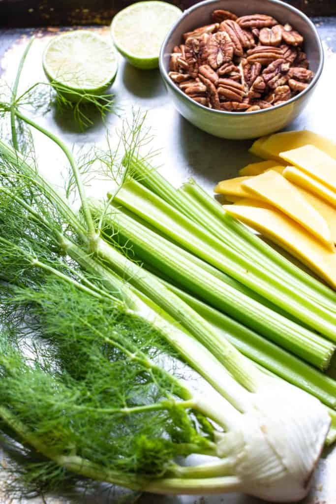 limes, pecans, fennel, mango and celery on a sheet pan