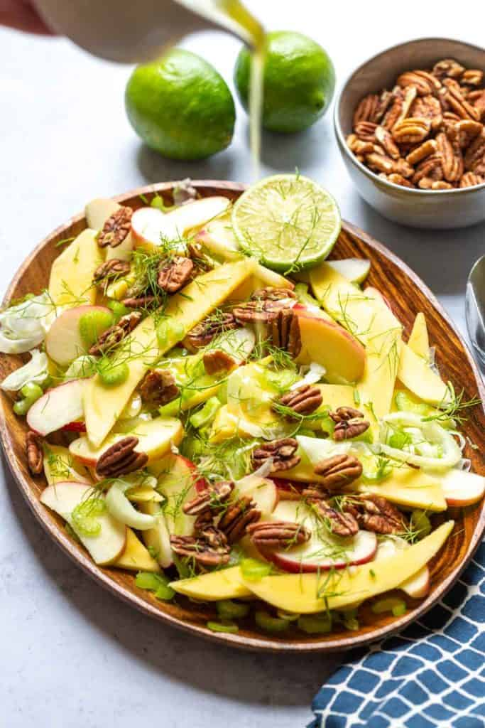 dressing being poured from above onto the fennel salad with pecans