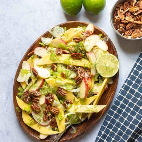 fennel salad on a brown plate with limes on the side