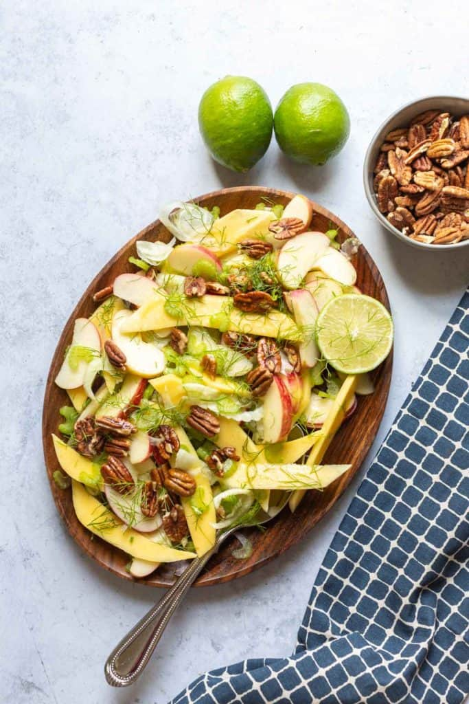 mango apple and fennel salad on a brown plate with bowl of pecans on side