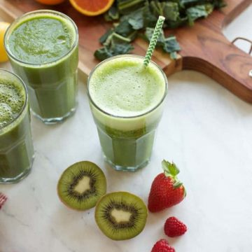 3 green smoothies in glasses with fruit on the side