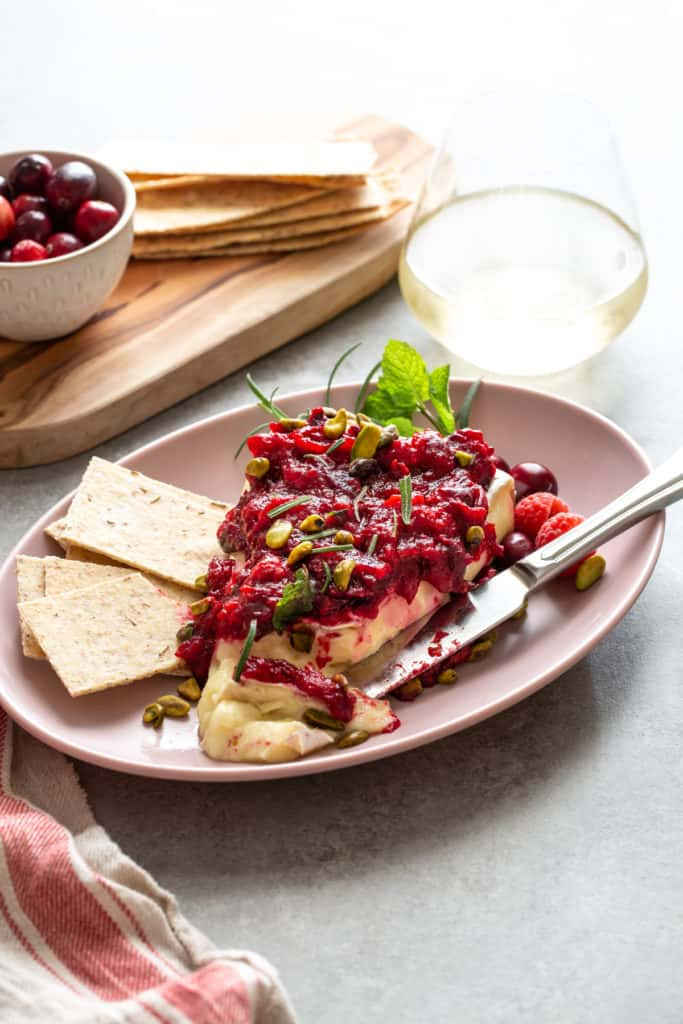 baked brie with raspberry sauce on a pink plate with crackers