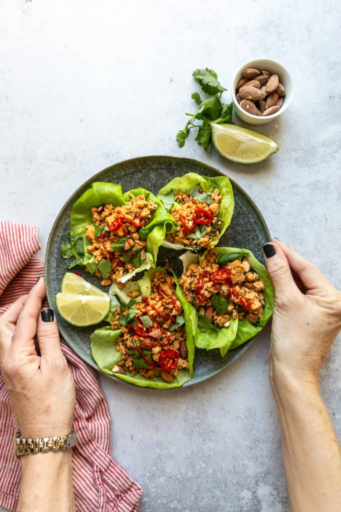 chicken lettuce wraps on plate with hands on sides