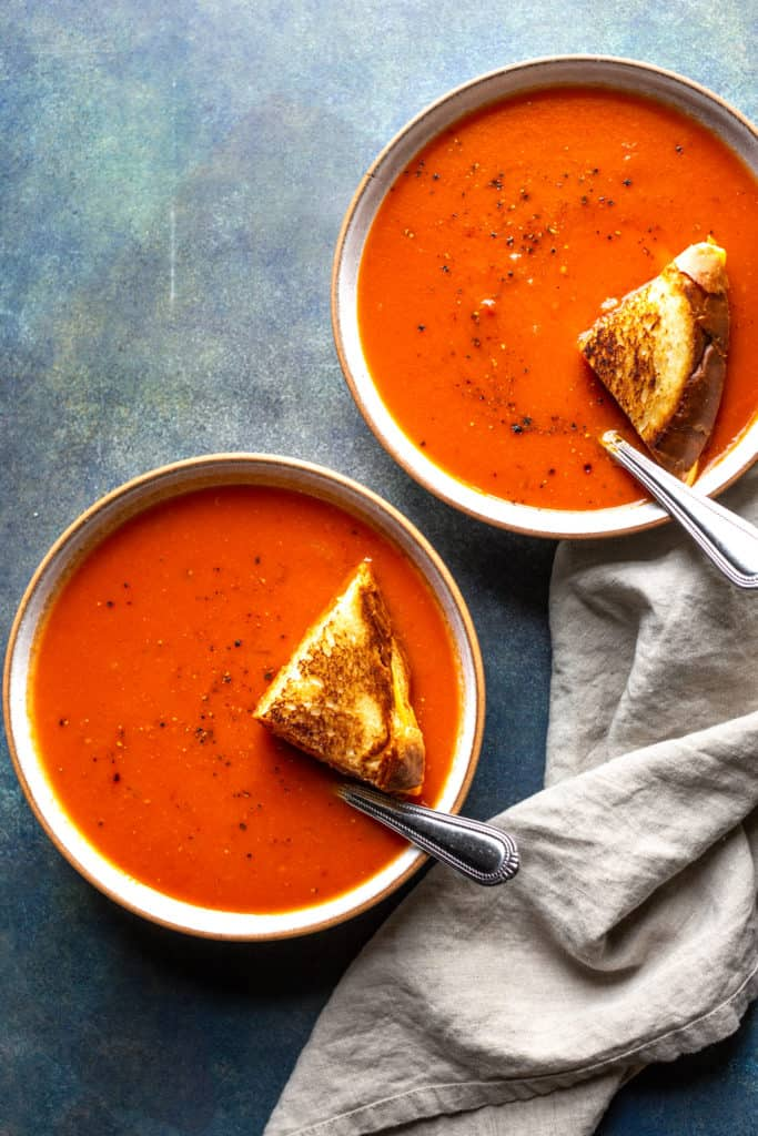 tomato soup in two bowls with grilled cheese on top
