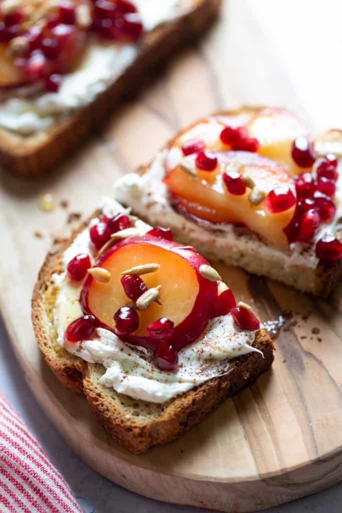 close up of toast with cream cheese plums and pomegranates