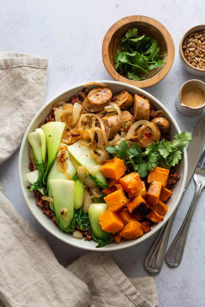 sausage grain bowl with tahini dressing and bok choy in a bowl