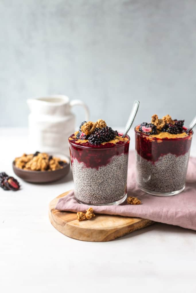 blackberry chia pudding in a glass with a spoon