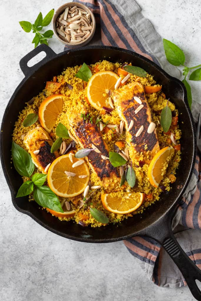 turmeric salmon and couscous with oranges in a black skillet