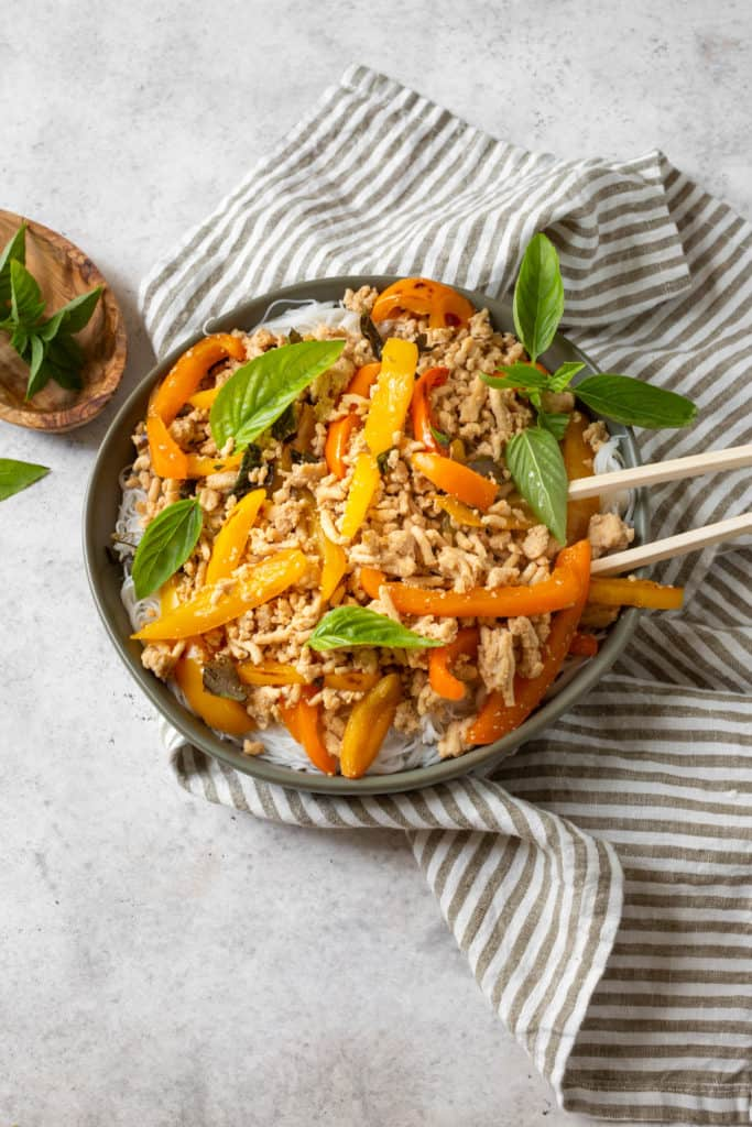 thai basil chicken with peppers and rice noodles in a bowl with chopsticks
